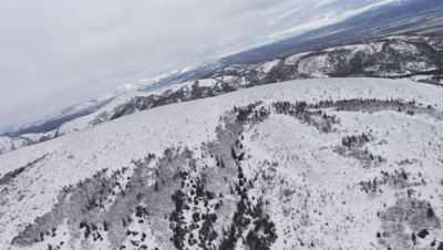 Aerial Over Snow-covered Ridge,Rise To Reveal Grand Vista of Mountain Range