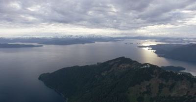 Wide Aerial Overlooking Rugged Alaska Coast,Mountain Range in distance
