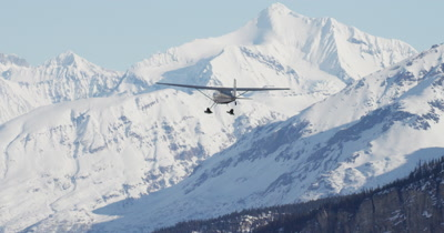 Aerial View of Small Airplane Flying in Alaska Mountains in Winter