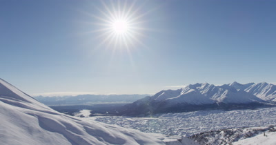 Aerial Snow-Covered Mountains and Possible Glacier in Alaska under Very Bright Sun
