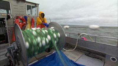 Commercial Fisherman Rolls Fishing Net Off Of Reel Into The Water On Bumpy Seas