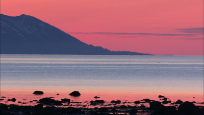 Brilliant Salmon Pink Sunset Over Mountains Alaska Peninsula With Rocky Inlet In Foreground