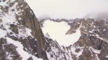 Exnice Cineflex Aeria Flight Over Brutal Snow Covered High Mountain Crags Slow Tilt From Vertical To Reveal Scope Of Range Horizontal Wide Shot