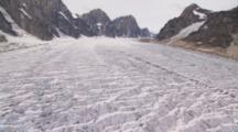 Low Altitude Cineflex Aerial Flight Over Alaska Glacier Forbidding Crags Ridges Brilliant Blue Fissures Tilt Up To Horizonal And Rocky Mountains Vertical Peaks On Edge Of Moraine