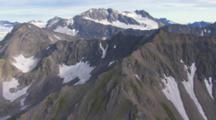 Aerial Cineflex Dramatic Mountain Realm Zoom To Family Of Mountain Goats Traverse High Ridge
