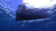 Skiff With Divers Shot Starts From Below And Ends On The Surface, On Calm Seas With Bue Sky