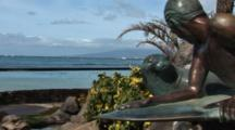 Statue Of Surfer & Monk Seal In Waikiki, Pan To Right, Ocean In Background