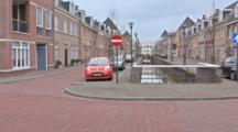A Small Dutch Town And And Brick Road.  Shot Pans Right As Auto Drives By.