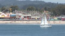 A Salboat Under Sail Near The Coast In Central California, Santa Cruz Boardwalk In The Background
