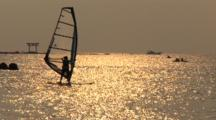 Hayama, Japan - Windsurfer Sails By Jetty In Shimmering Light