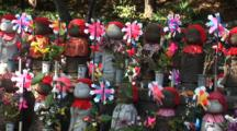 Tokyo, Japan - A Shrine With Many Statues Of Children Holding Windmills, Pans Right