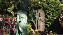 Tokyo, Japan - A Shrine With Statue And Flowers, Tilt Up