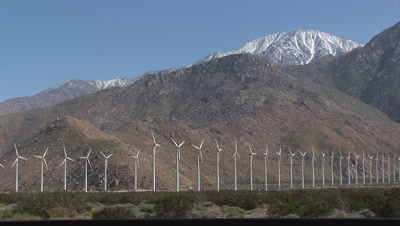 Wind Turbine Front Lit At Base Of Snow Capped Mountains, Shot Pans To The Right