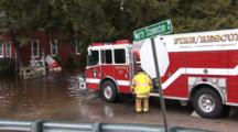 Major Flooding In A Small New England Town, House Stands In The Middle Of A River, Fire Engine In Forground, Pan To Left