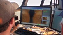 Side Scan Sonar Operator Talking On Handheld Radio While Watching Displays