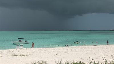 Tropical Beach, Lagoon And Stormy Sky, People Swim In Water Near The Boats