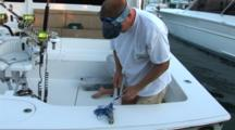 Fishing - Angler Prepares For A Billfish Tournament By Sharpening A Hook On A Fishing Leader