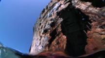 Underwater Exterior Shot Of A Ship Wreck Sitting On Bottom In Shallow Water, Camera Looking Upward & Breaks The Surface Revealing Bow, Large Schools Of Fish.