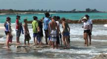 Eco-Tour Guests Standing On A Rocky, Tropical Sea Shore With Breaking Waves