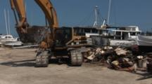 Heavy Construction Equipment Rolls Away From The Remnants Of A Destroyed Boat