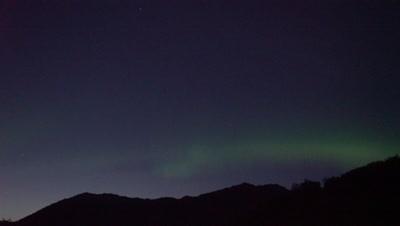 4K Northern Lights in summer sky pan above mountains Aurora Borealis - NO Colour Correction