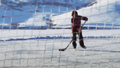 Young boy playing hockey; shoots, slides onto the ice.
