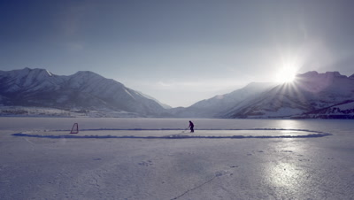 Someone playing hockey on a frozen pond.