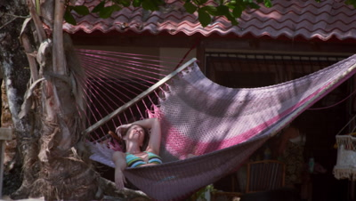 Bikini-clad woman swings in hammock at beachfront house