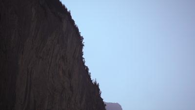 Long shot of paraglider falling off mountain