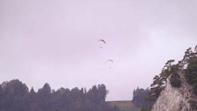 Long distance shot of two paragliders hovering over trees in Switzerland