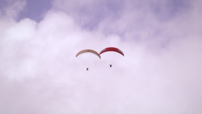 Long distance shot of two paragliders soaring side by side in Switzerland