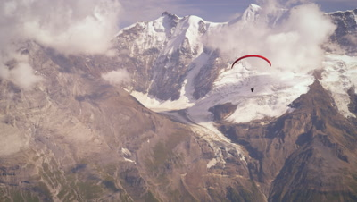 Shot of a paraglider passing the Swiss alps