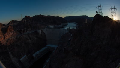 Timelapse shot of the sunrise over the Hoover Dam in Nevada with lens flare