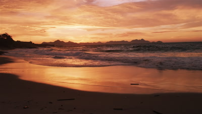 Slow motion tracking shot of huge waves crashing on Devil's beach (Praia do Diabo) at sunset
