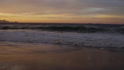 Slow motion, reverse pan shot of waves flowing on to Praia do Diabo (Devil's Beach)