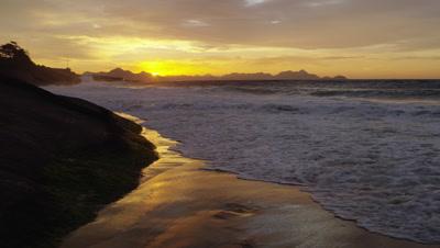 Slow-mo, static shot of killer waves hitting the beach and cliffs at Praia do Diabo (Devil's Beach)