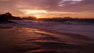 Slow motion, tracking shot of the waves crashing on the surf of praia vermelha (Devil's Beach)