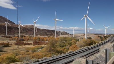 Nine wind turbines in a canyon seen from behind.