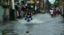 Motorbike Drives Through Flooded City Street