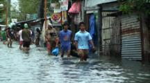 People Walk Through Flooded City Street