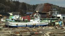 Japan Tsunami Aftermath - Survivors Walk Past Boat Washed Up In Kesennuma City