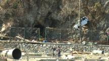 Japan Tsunami Aftermath - Survivors Walk Past Car Stuck Up Cliff In Kesennuma City