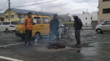 Japan Tsunami Aftermath - Survivors Stand Around Fire On Street In Ishinomaki City