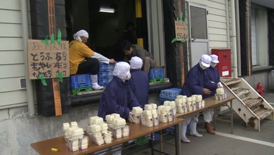 Japan Tsunami Aftermath - Survivors Collect Supplies From Factory In Osaki City