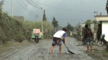 Man Scrapes Volcanic Ash Mud Off Road After Major Eruption