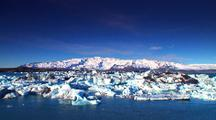 Glacier With Ice Chunks In Blue Water