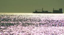 Ship In Silhouette On Sparkling Water