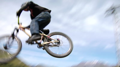 A Slow Motion Shot Of A Mountain Biker Doing A 360 Off A Drop.