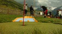 Several Boys Playing Mini Golf, One Shots And Misses.