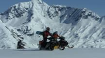 Three Snowmobilers Ride Slowly Together.